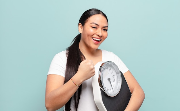 Hispanic woman feeling happy, positive and successful, motivated when facing a challenge or celebrating good results