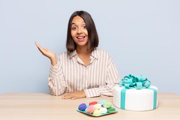 Латиноамериканская женщина чувствует себя счастливой, удивленной и веселой, улыбается с позитивным настроем, реализует решение или идею