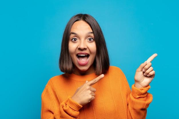 Латиноамериканка чувствует себя радостной и удивленной, улыбается с шокированным выражением лица и указывает в сторону
