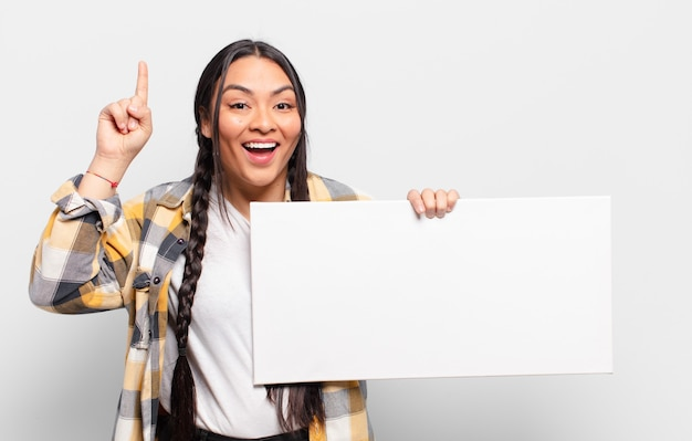 Hispanic woman feeling like a happy and excited genius after realizing an idea, cheerfully raising finger, eureka!