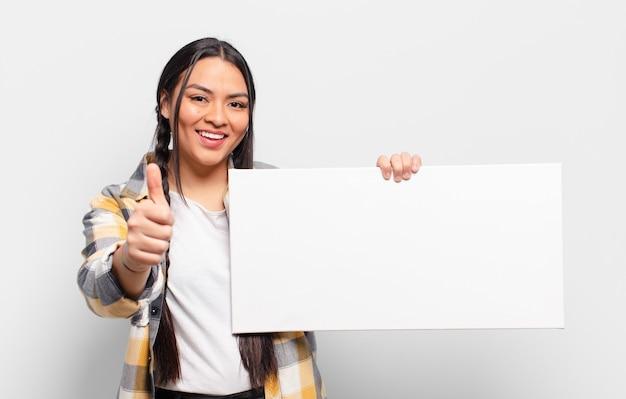 Латиноамериканская женщина чувствует себя гордой, беззаботной, уверенной и счастливой, позитивно улыбается и показывает палец вверх