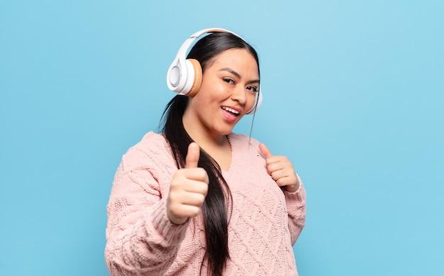 ヒスパニック系の女性は、誇り高く、気楽で、自信があり、幸せで、親指を立てて積極的に微笑む
