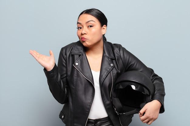 ヒスパニック系の女性は、困惑して混乱している、疑っている、重みを付けている、または面白い表現でさまざまなオプションを選択している