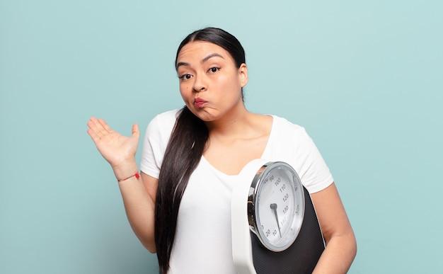 Латиноамериканская женщина чувствует себя озадаченной и сбитой с толку, сомневается, взвешивает или выбирает разные варианты со смешным выражением лица