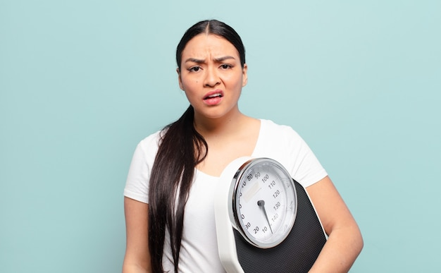 예상치 못한 무언가를 바라 보는 멍청하고 기절 한 표정으로 의아해하고 혼란스러워하는 히스패닉계 여성