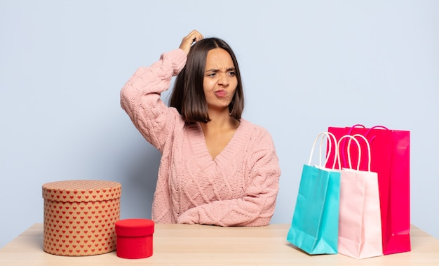 Hispanic woman feeling puzzled and confused, scratching head and looking to the side