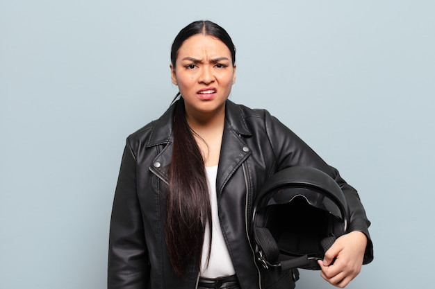 Hispanic woman feeling puzzled and confused, with a dumb, stunned expression looking at something unexpected