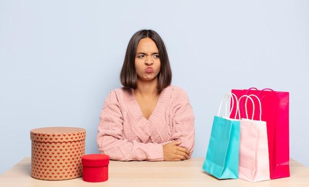 히스패닉계 여성이 슬프거나 화를 내거나 화를 내고 부정적인 태도로 옆을 바라보고 의견이 일치하지 않습니다.