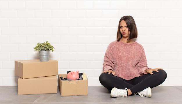 Латиноамериканская женщина грустит, расстроена или злится, смотрит в сторону с негативным отношением и хмурится в знак несогласия.