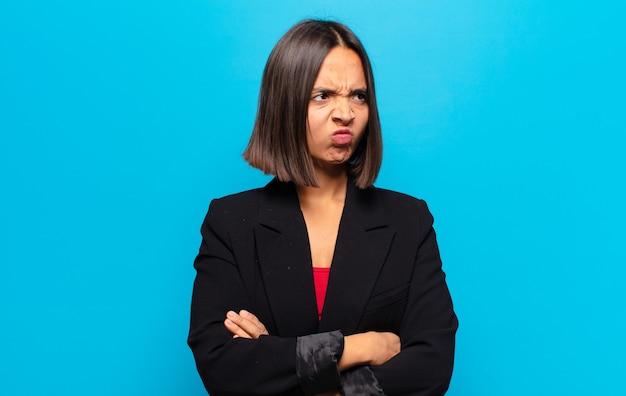 ヒスパニック系の女性は、悲しみ、動揺、または怒りを感じ、否定的な態度で横を向いて、意見の相違に眉をひそめています