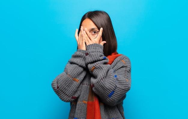 Латиноамериканская женщина чувствует себя напуганной или смущенной, подглядывает или шпионит с полузакрытыми руками глазами