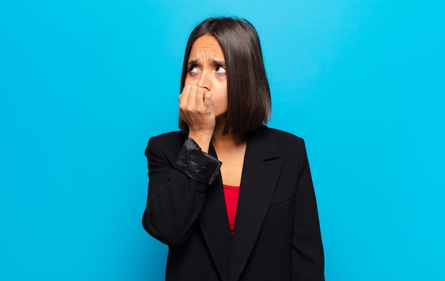 Hispanic woman feeling serious, thoughtful and concerned, staring sideways with hand pressed against chin