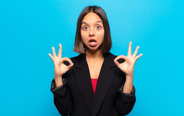 히스패닉계 여성이 충격을 받고 놀란 느낌이 들며 양손으로 괜찮은 기호를 만드는 승인을 보여줍니다.