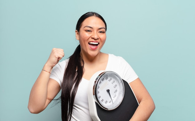 Hispanic woman feeling shocked, excited and happy, laughing and celebrating success, saying wow!