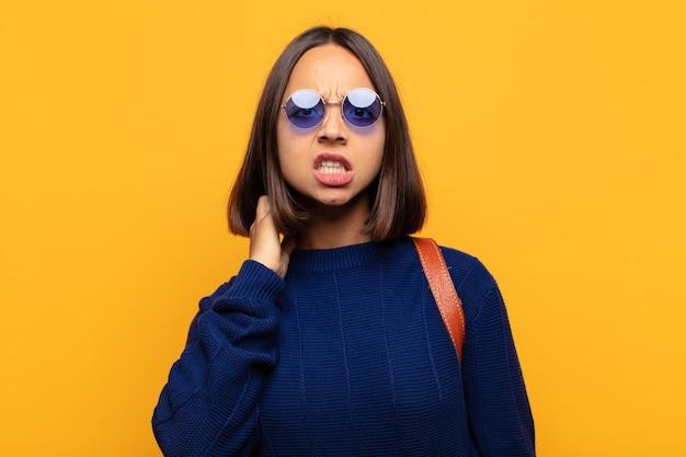 ヒスパニック系の女性は、ストレス、欲求不満、倦怠感を感じ、痛みを伴う首をこすり、心配し、問題を抱えた表情で