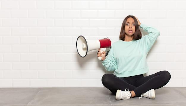 ヒスパニック系の女性がストレス、心配、不安、恐怖を感じ、頭に手を当てて、誤ってパニックに陥
