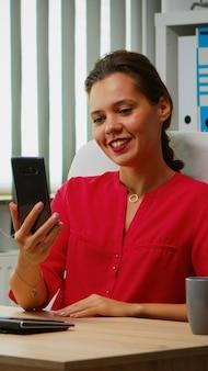 現代のオフィスに座って電話でオンライン会議をしているヒスパニック系の女性。マネージャーがビジネスリモートチームと協力して、仮想会議、インターネットテクノロジーを使用したウェビナーでのチャットについて話し合っています