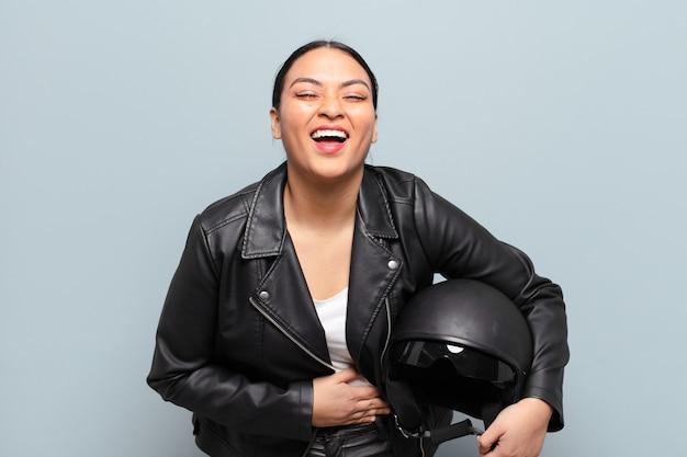 いくつかの陽気な冗談で大声で笑い、幸せで陽気に感じ、楽しんでいるヒスパニック系の女性