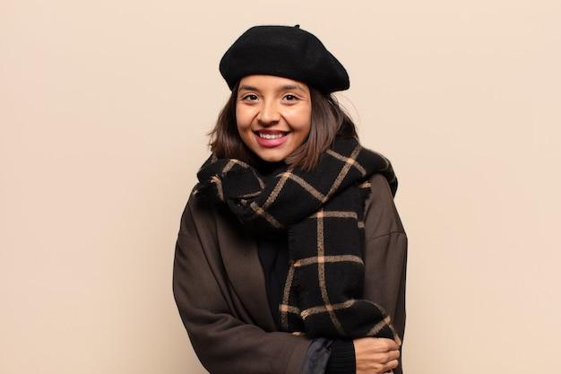 Латиноамериканка застенчиво и весело смеется, с дружелюбным и позитивным, но неуверенным в себе отношением