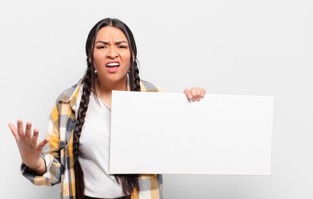 Латиноамериканская женщина выглядит сердитой, раздраженной и разочарованной и кричит