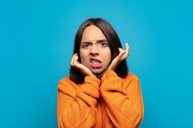 Латиноамериканская женщина выглядит сердитой, напряженной и раздраженной, закрывает оба уха оглушительным шумом, звуком или громкой музыкой.