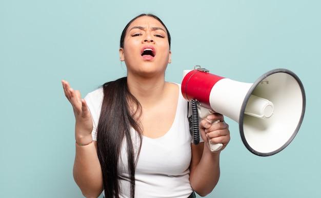 Латиноамериканская женщина выглядит отчаявшейся и разочарованной, напряженной, несчастной и раздраженной, кричит и кричит