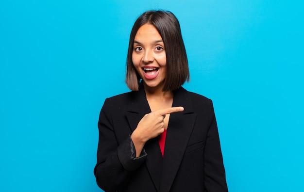 スペースをコピーするために横と上を指して興奮して驚いたように見えるヒスパニック系の女性