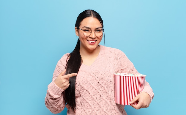 Hispanic woman looking excited and surprised pointing to the side and upwards to copy space