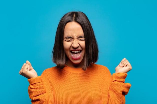 Латиноамериканская женщина выглядит очень счастливой и удивленной, празднует успех, кричит и прыгает