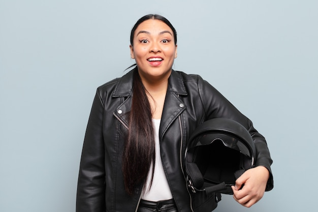幸せそうに見えて嬉しそうに驚いて、魅了されてショックを受けた表情で興奮しているヒスパニック系の女性