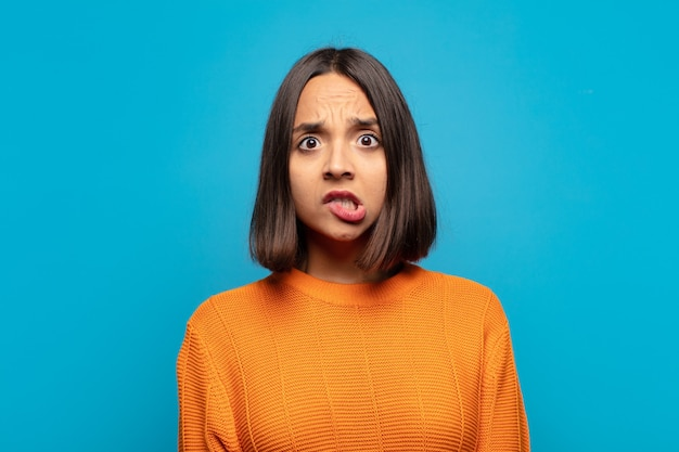 Латиноамериканская женщина выглядит озадаченной и сбитой с толку, нервно прикусывает губу, не зная ответа на проблему
