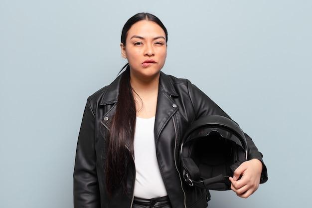 困惑して混乱しているように見えるヒスパニック系の女性、神経質なジェスチャーで唇を噛んでいる、問題の答えを知らない
