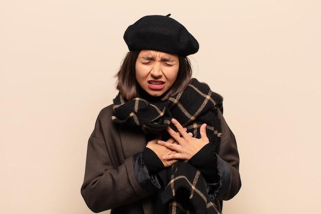 Латиноамериканка выглядит грустной, обиженной и убитой горем, держит обе руки близко к сердцу, плачет и чувствует себя подавленной.