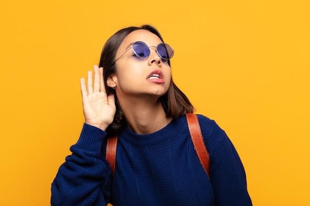Латиноамериканка выглядит серьезной и любопытной, слушает, пытается услышать секретный разговор или сплетню, подслушивает