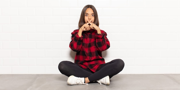 Hispanic woman looking serious and displeased with both fingers crossed up front in rejection, asking for silence