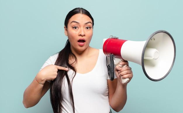 ヒスパニック系の女性がショックを受け、口を大きく開いて驚いて、自分を指さしている