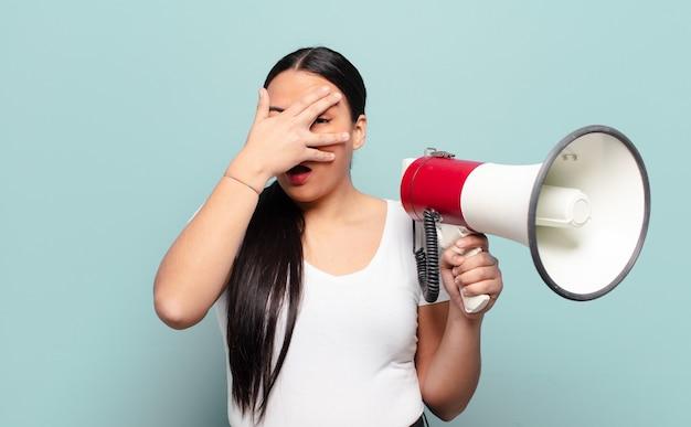 ヒスパニック系の女性がショックを受けたり、怖がったり、恐怖を感じたり、顔を手で覆ったり、指の間をのぞいたり