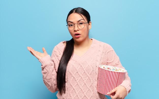 Латиноамериканская женщина выглядит удивленной и шокированной, с отвисшей челюстью, держащей объект открытой рукой сбоку