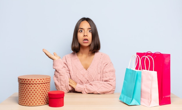 Hispanic woman looking surprised and shocked, with jaw dropped holding an object with an open hand on the side