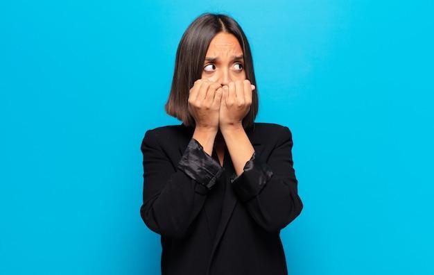 히스패닉계 여성이 걱정, 불안, 스트레스 및 두려워, 손톱을 물어 뜯고 측면 복사 공간을 찾고
