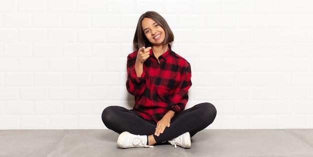 満足のいく、自信を持って、フレンドリーな笑顔でカメラを指して、あなたを選ぶヒスパニック系の女性