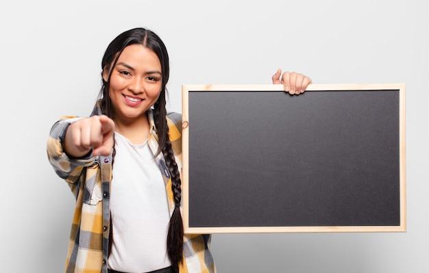 Латиноамериканская женщина с довольной, уверенной, дружелюбной улыбкой, указывая на камеру, выбирает вас