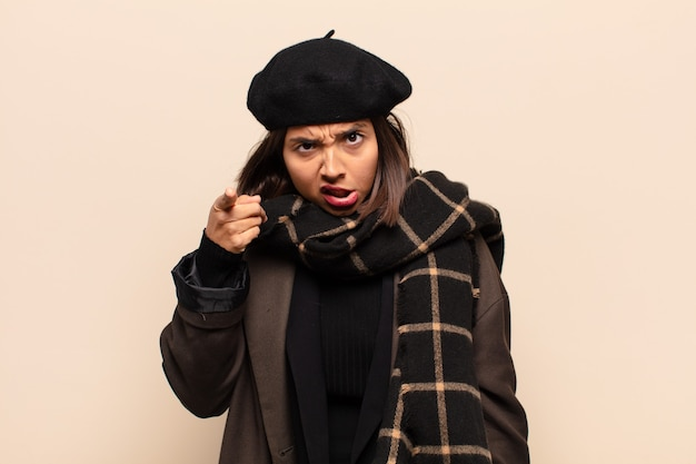 猛烈な狂気のボスのように見える怒っている攻撃的な表情でカメラを指しているヒスパニック系の女性