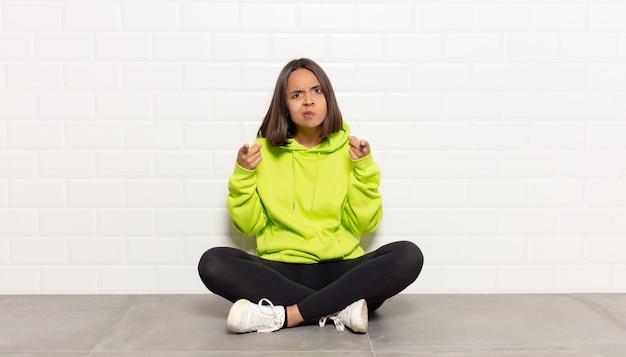 両指と怒りの表情で前を向いて、義務を果たすように言っているヒスパニック系の女性