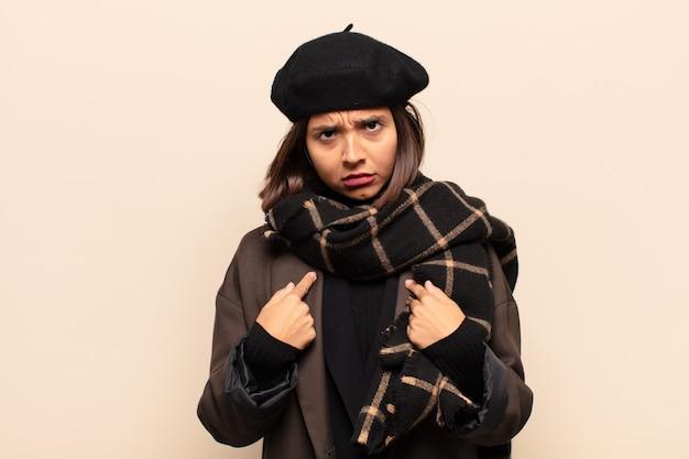 혼란스럽고 익살스러운 표정으로 자기를 가리키는 히스패닉계 여성