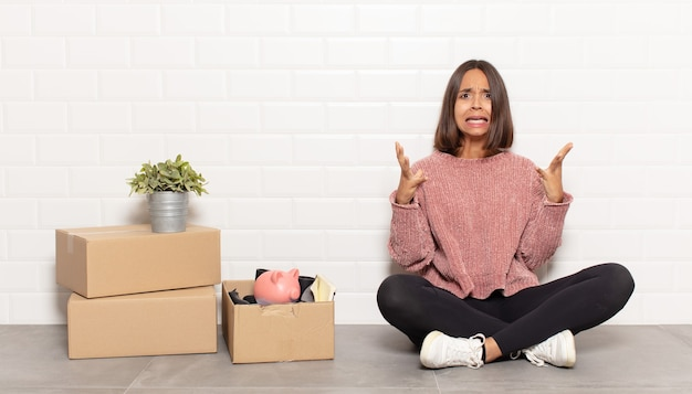 Латиноамериканская женщина кричит с поднятыми руками, чувствуя ярость, разочарование, стресс и расстройство