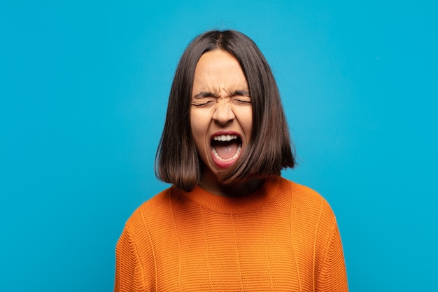 Латиноамериканка агрессивно кричит, выглядит очень сердитой, расстроенной, возмущенной или раздраженной, кричит