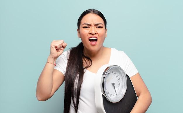 Латиноамериканская женщина агрессивно кричит с гневным выражением лица или со сжатыми кулаками празднует успех