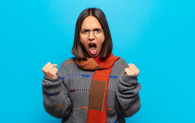 화가 난 표정으로 또는 주먹으로 공격적으로 외치는 히스패닉계 여성이 성공을 축하합니다.