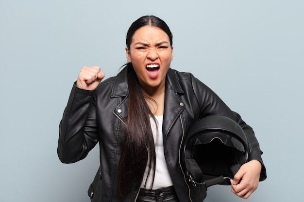 Hispanic woman shouting aggressively with an angry expression or with fists clenched celebrating success